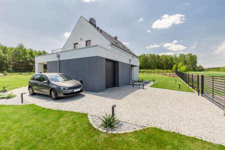 주차 된 자동차와 함께 작은 현대 집의 외관