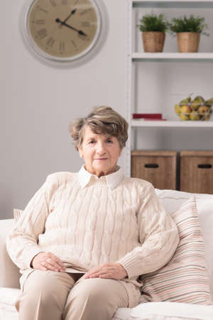 cosy: Elderly woman sitting and resting on couch in cosy room Stock Photo