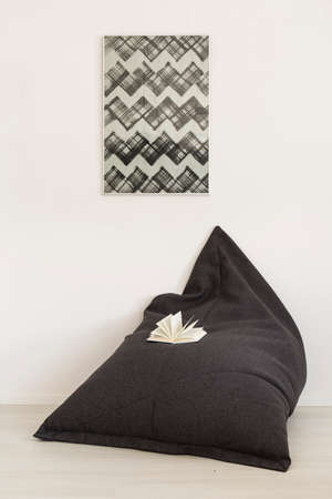 bright paintings: Shot of a black bag chair lying on the white floor in a modern interior