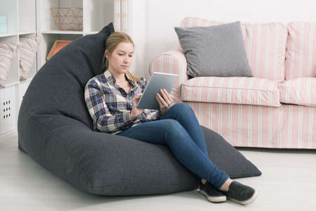 beanbag: Young woman sitting in a grey beanbag with her tablet in a cosy room arranged in white and pink