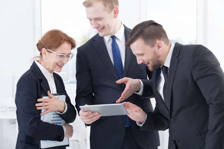 business project: Business people reading new business project on tablet
