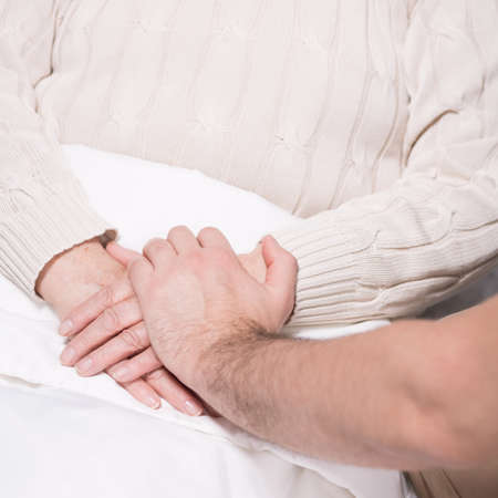 Close-up of supportive man holding grandmothers hand
