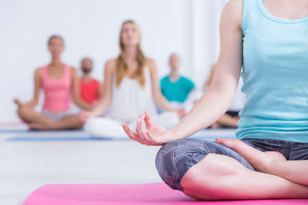 El primer tiró de una mujer en ropa deportiva sentado en una alfombra de color rosa y hacer yoga