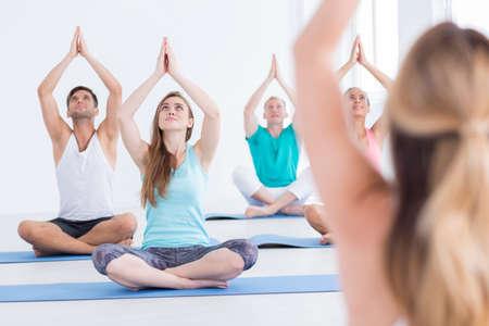 Disparo de un grupo de personas sentadas en sus esteras durante la clase de yoga