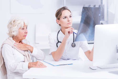 chest xray: Pulmonologist analyzing senior patients chest x-ray picture Stock Photo