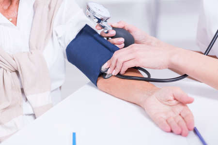 Close up of a doctor taking patients blood pressure Stock Photo