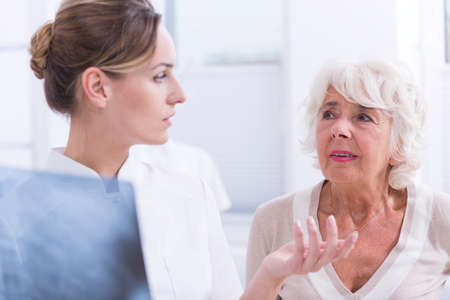 orthopedist: Young orthopedist holding x-ray picture talking with a worried senior patient Stock Photo
