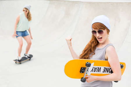 girls youth: Shot of a girl with long hair holding a skateboard and clenching her fist