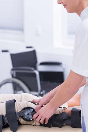 orthopedist: Orthopedist and patient with knee orthosis, wheelchair in the background