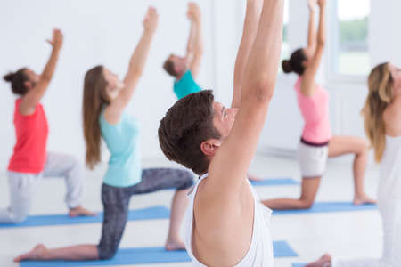 Closeup shot of a man with raised hands with yoga group in the background Archivio Fotografico