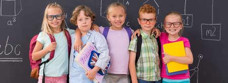 niño escuela: Felices los niños de primaria con la pizarra en el fondo Foto de archivo