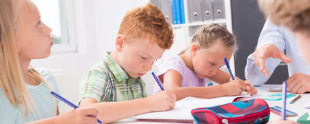 elementary school: Primary school children solving math problem at the desk Stock Photo