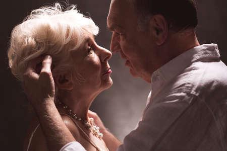 Ouder echtpaar die aech andere met man hand op het haar van de vrouw bekijken