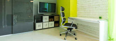 home office interior: Panoramic shot of a home office interior with a minimalistic white desk and a TV Stock Photo