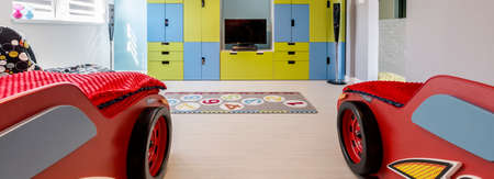 storage unit: Cropped shot of a childrens room with red car beds and a colorful storage unit