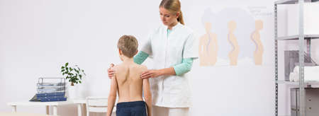 curvature: Young female spine care specialist and little child Stock Photo