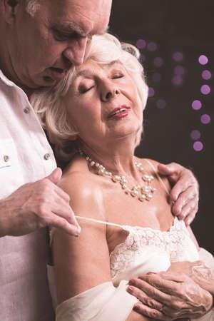 Shot of elder couple, when man is standing behind woman and stripping shoulder-strap of her underwear