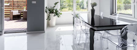 dining table and chairs: Panoramic shot of a dining area with a black polished table and transparent chairs