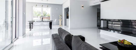 Shot of a spacious living room combined with a dining area, designed in bright tones
