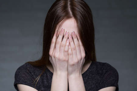 express feelings: Portrait of long haired girl, who is covering her face by hands Stock Photo