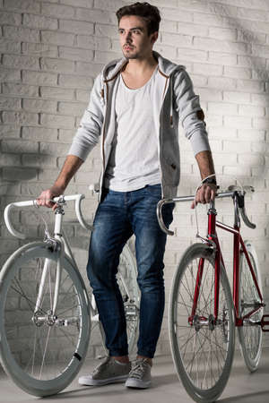 Young handsome men standing in a bright interior with two hipster bicycles on his right and left site