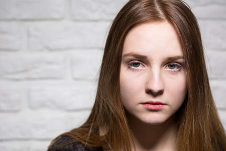 ordinary: Close shot of bored, long haired and blue-eyed girls face, at the brick wall background