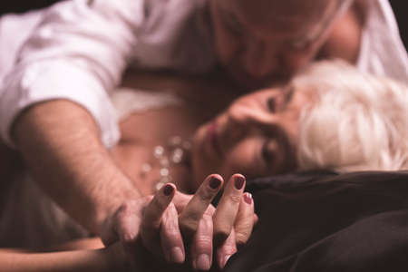 Elder couple lying together on a bed in an erotic love hug with intertwined fingers Stock Photo
