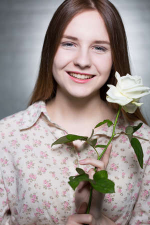 Portrait of long haired and blue-eyed girl, who is smiling and holding a white rose