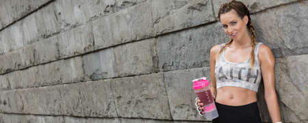 energy drink: Shot of a young sportswoman standing against a concrete wall and holding an energy drink