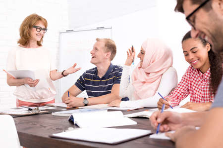 beside table: Mature teacher and foreign students sitting beside table in light classroom Stock Photo