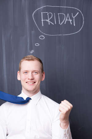 smartly: Portrait of an enthusiastic office worker in front of a blackboard with Friday written on it