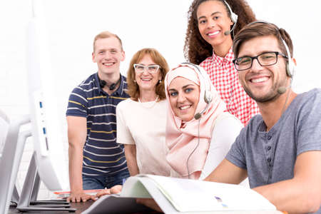 qualifications: Young people from students exchange program and mature IT teacher Stock Photo