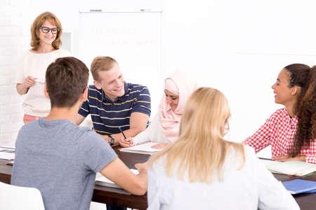 emigranti: Gruppo di emigranti seduto in aula luce durante corso di lingua con donna matura positivo Archivio Fotografico