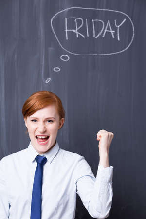 smartly: Portrait of a young office worker shouting enthusiastically in front of a chalk Friday writing on a blackboard