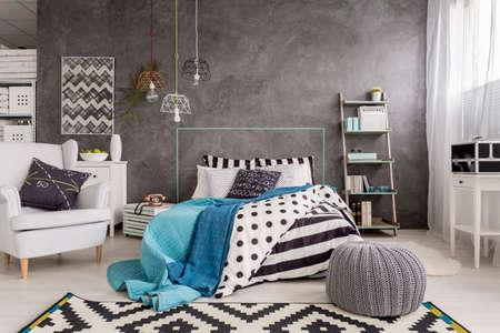 Ruime nieuw ontwerp slaapkamer met tapijt, een leunstoel, een groot bed en decoratieve wandafwerking Stockfoto