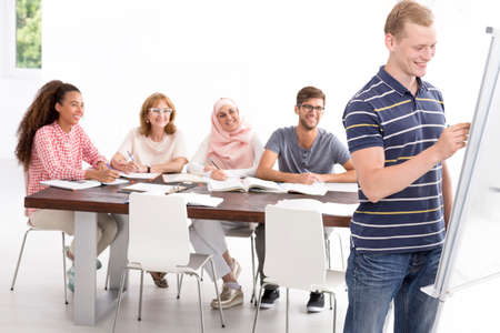 beside table: Young man writing on a whiteboard, in the background multicultural group sitting beside table Stock Photo