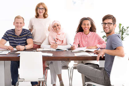 Group of people of different nationalities during language course with mature teacher Standard-Bild