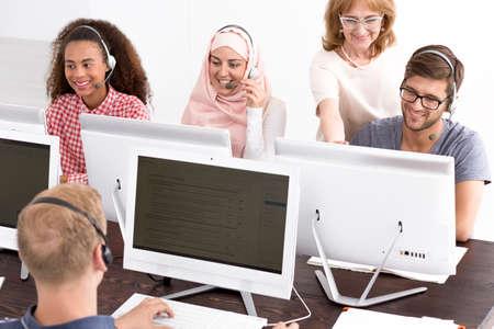 jovenes estudiantes: profesor de TI madura y jóvenes estudiantes que se sientan delante de las computadoras con auriculares