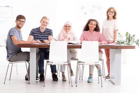 emigranti: insegnante maturo e gruppo di giovani emigranti studiare lingue straniere