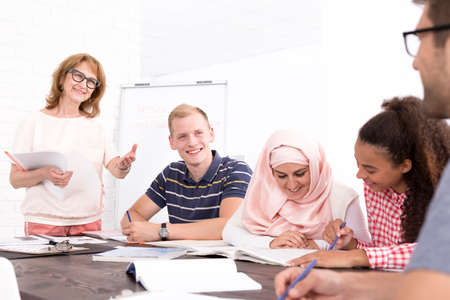 Group of young people and mature teacher during classes in light interior