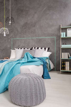 pouf: Grey bedroom with comfortable pouf, bed, and decorative wall finish
