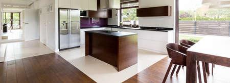 Gemeinsamer Raum von einer offenen Küche und Essbereich mit Holztisch Standard-Bild - 61602097