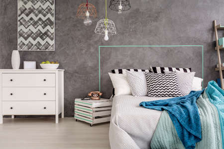 bedroom furniture: Stylish bedroom with white furniture and decorative wall plaster Stock Photo