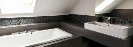Vasca da bagno rettangolare e lavandino in bagno ben illuminato Archivio Fotografico