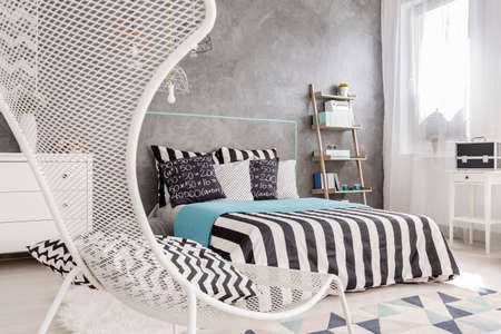 bedroom wall: Modern bedroom with white chair, large bed and decorative wall finish