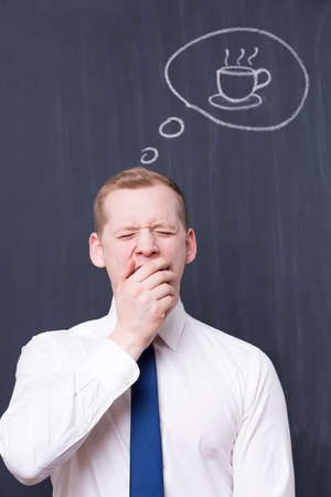smartly: Yawning office worker in front of a blackboard with a cup of coffee drawn on it