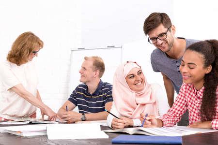 idiomas: Grupo de jóvenes felices de diferentes nacionalidades que trabajan juntos Foto de archivo