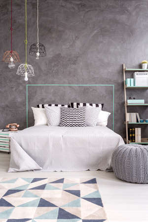 bedroom wall: Grey bedroom with carpet, stylish pendant lamp and decorative wall plaster Stock Photo