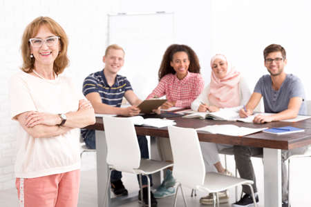 qualifications: Happy mature teacher and her multicultural class