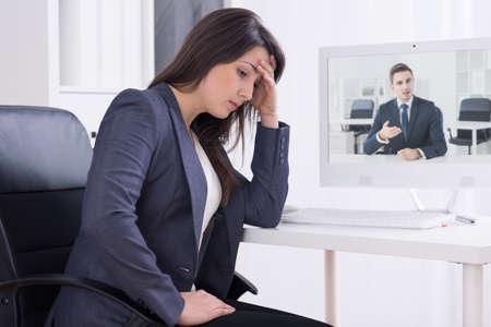 molesto: mujer joven en el trabajo, sintiendo un dolor de cabeza molesto